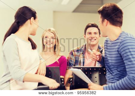 education, high school, teamwork and people concept - group of smiling students with notebook sitting in lecture hall and talking