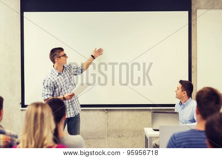 education, high school, technology and people concept - smiling student boy in glasses with notepad, laptop computer standing in front of students and teacher in classroom
