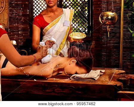 Woman and two masseuses having Indian massage with pouch of rice.