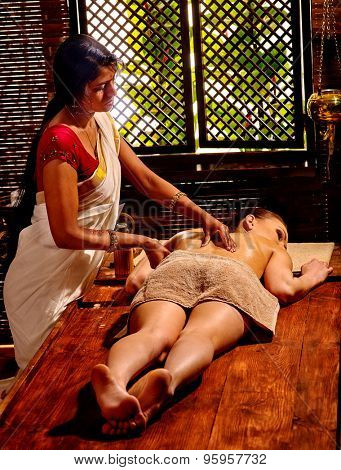 Young white woman having oil Indian spa treatment.
