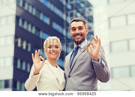 business, partnership, gesture success and people concept - smiling businessman and businesswoman making ok gesture over office building