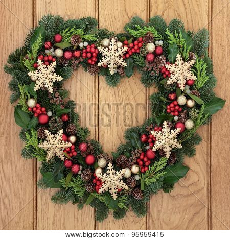 Christmas heart shaped wreath with gold snowflake bauble decorations, holly, mistletoe and winter greenery over oak front door background.