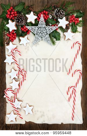 Christmas abstract background border with gingerbread biscuits and candy canes, holly and winter greenery  on parchment paper over old oak wood.