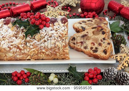 Stollen christmas cake with red and gold bauble decorations, holly and winter greenery.