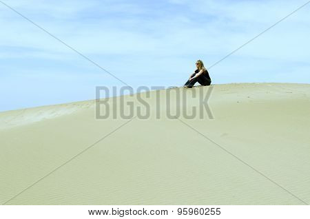 Girl Sitting On Top Of A Dune