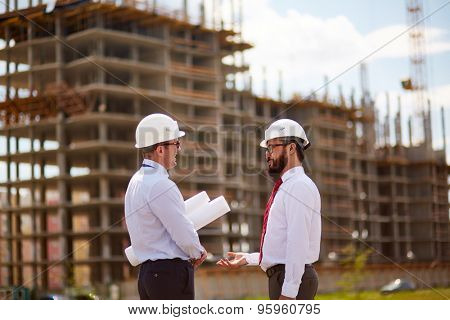 Small group of businessmen in helmets and formalwear talking in front of unfinished construction
