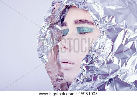 Portrait of pretty woman wrapped in foil looking forward standing on light grey background