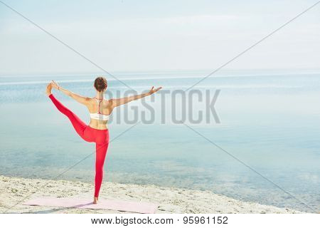 Sporty female in activewear stretching her leg while standing on the beach