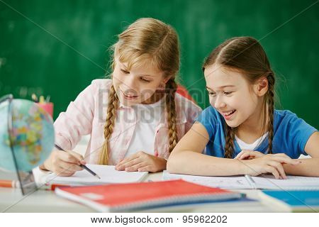 Two cute schoolgirls drawing together at lesson