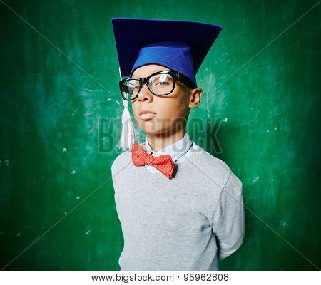 Serious graduate in eyeglasses looking at camera