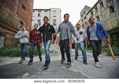 Group of spiteful hooligans walking along grunge brick houses