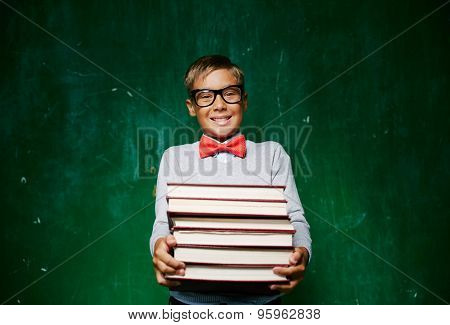 Happy schoolboy with stack of books looking at camera