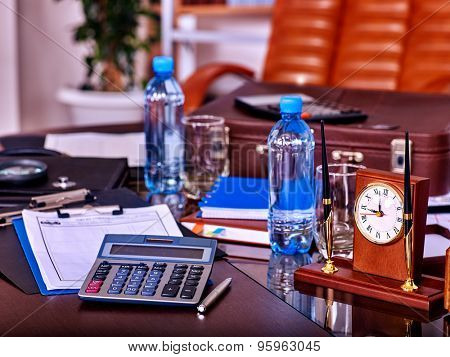 Business still life with stationery and clock on table in office. Bottle water.