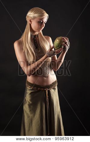 beautiful woman in dress holding a dragon egg in hands