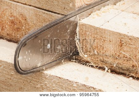 Chainsaw cutting wooden beam