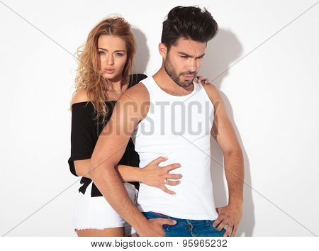Hot casual man holding his hands in pockets, looking down while his girlfriend is holding him from behind.