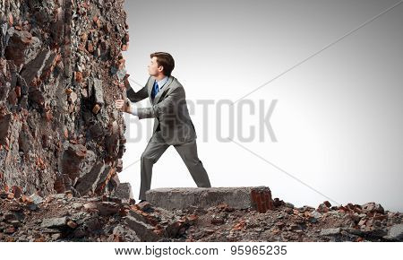 Businessman making effort to move stone wall