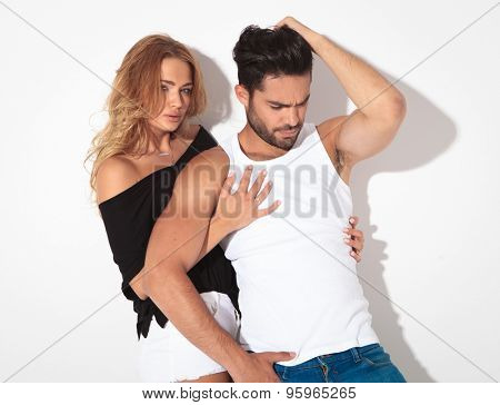 Blonde woman looking at the camera while embracing her lover. He is fixing his hair while looking down.