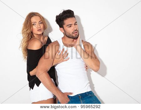 Handsome casual man peting his beard while his lover is holding him.