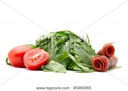 Fresh rocket with one whole and one cut in half cherry tomato and rolled prosciutto
