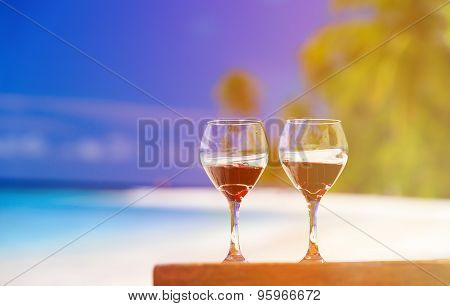 two wine glasses on sand beach