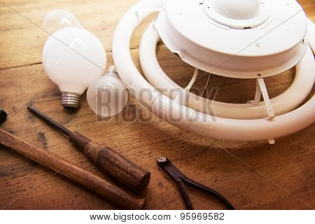 Replacing obsolete or old lighting equipment. Incandescent lamp or light bulbs and flourscent lamps on a old wooden desk with  screw drivers and other hand tools.