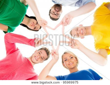 Happy students in colorful clothing standing together making star with their fingers.