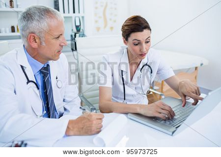 Concentrated medical colleagues discussing and pointing on laptop screen in the hospital
