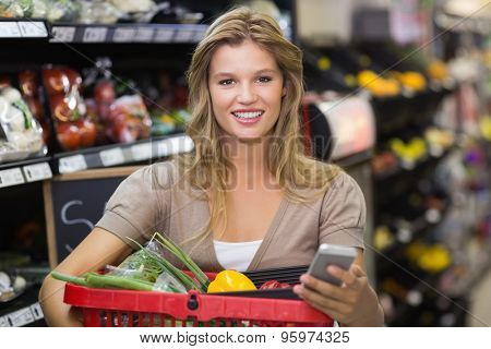 Portrait of smiling blonde woman buying vegetales and uding her smartphone at supermarket