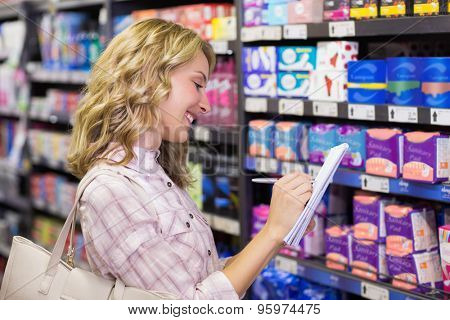 Side view of a happy smiling blonde woman writing on her notepad in supermarket