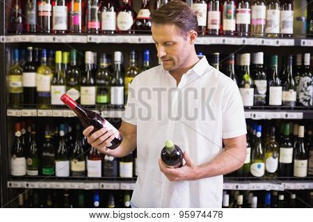 A handsome looking at wine bottle in supermarket