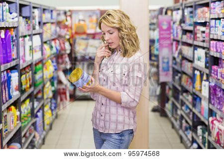Side view of a pretty blondfe woman looking at a product in supermarket