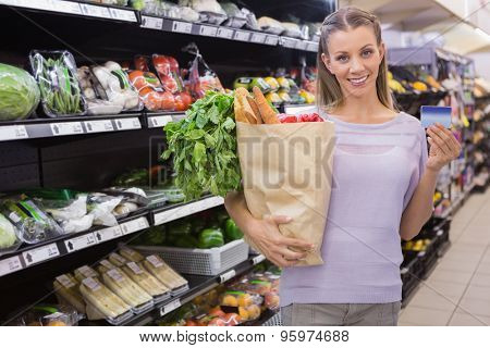 Pretty blonde woman holding bag and credit card in supermarket