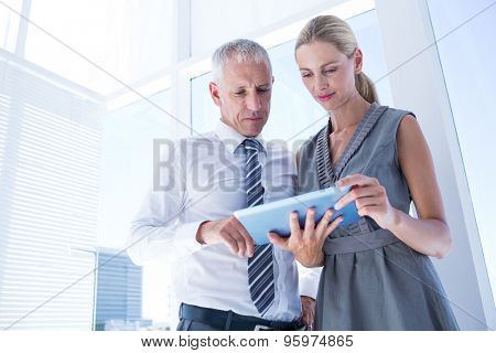 Business people discussing over a digital tablet in the office
