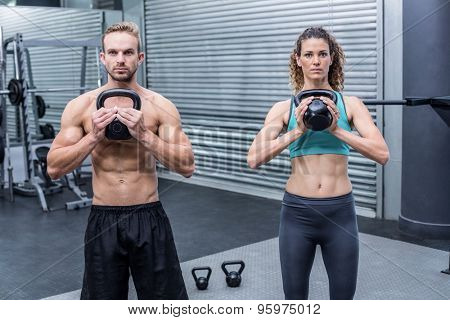 Muscular couple exercising with kettlebells at the crossfit gym