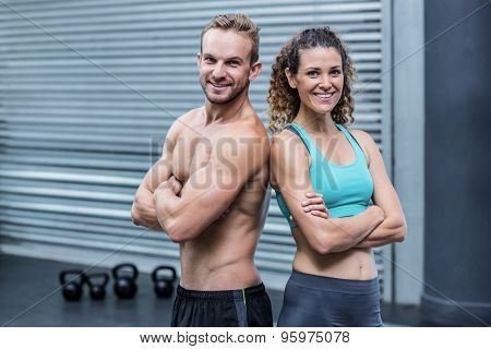 Muscular couple giving back to back with crossed arms