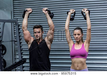 Muscular couple lifting kettlebells at the crossfit gym