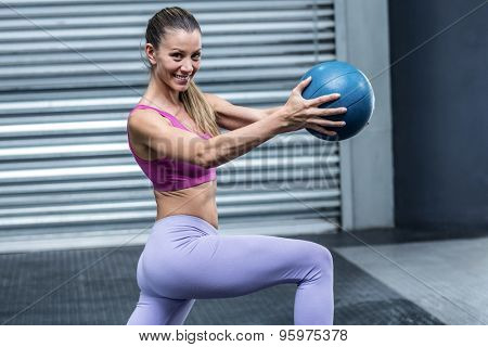 Portrait of a muscular woman doing ball exercises