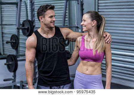 Muscular couple looking at each other with arms around