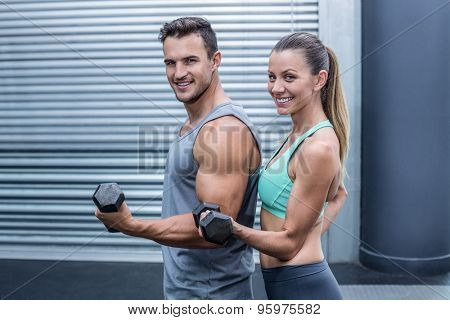 Portrait of a muscular couple lifting dumbbells