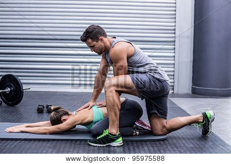 Muscular couple doing a body stretching at the crossfit gym