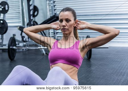 Muscular woman doing abdominal crunch at the crossfit gym