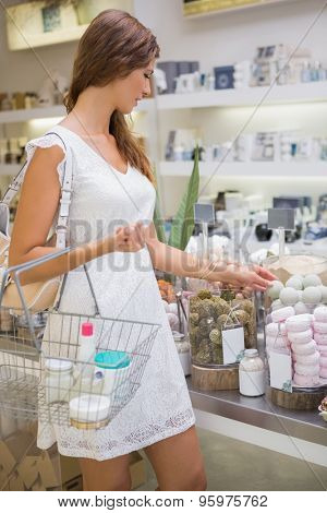 Woman with shopping basket testing soap at a beauty salon