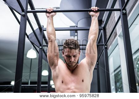 Muscular man doing pull ups in crossfit gym