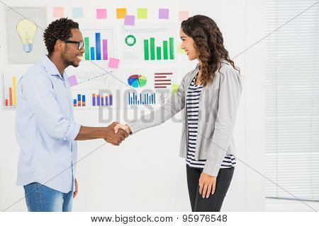 Young smiling business people shaking hands in the office