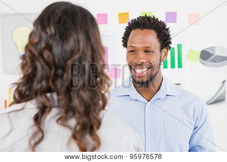 Young smiling business man looking at the woman in front of him in the office