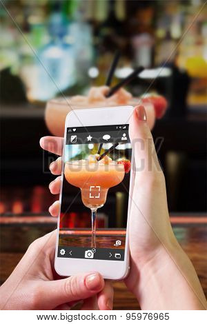 Hand holding smartphone against close up on colourful frozen daiquiri