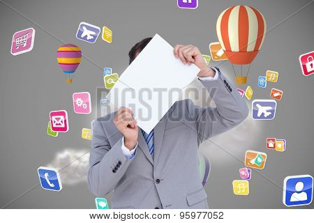 Businessman holding blank sign in front of his head against cloud computing graphic with hot air balloons
