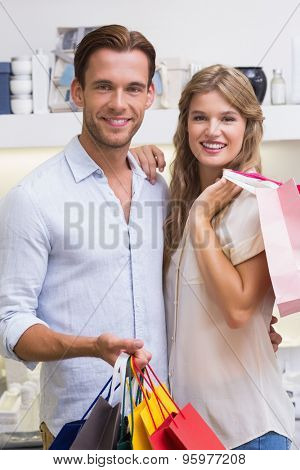 Portrait of a happy smiling couple with bags in the perfumery