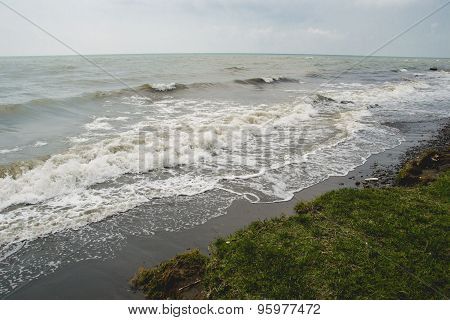 landscape by the sea, choppy water,  lowering sky, toned